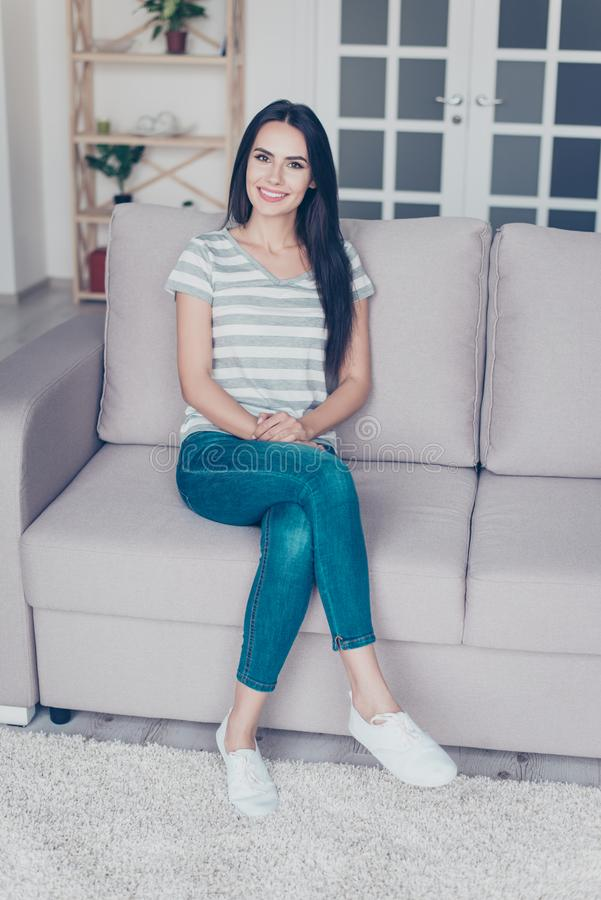 Vertical portrait of cute pretty smiling woman sitting with crossed legs on a sofa at home royalty free stock photography