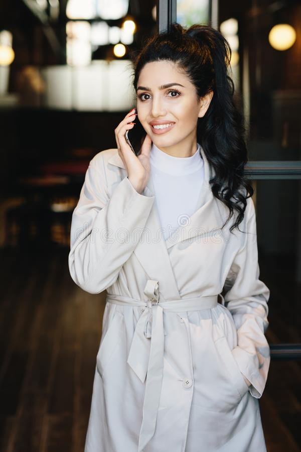Vertical portrait of elegant brunette businesswoman in white coat communicating over cell phone while standing outdoors. stock photo