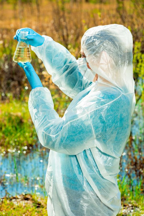 Vertical portrait of an environmentalist in protective clothing during work - lake water. Research stock photography