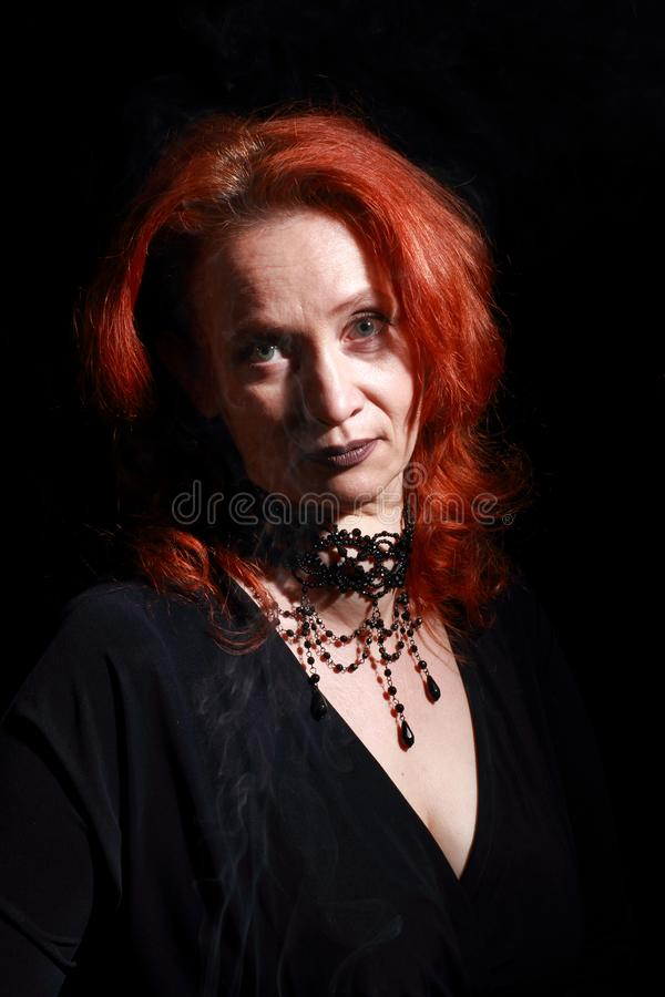 Vertical portrait of fine emotional redhead witch. Magical decorations and live expressions. Black wizard background royalty free stock photo
