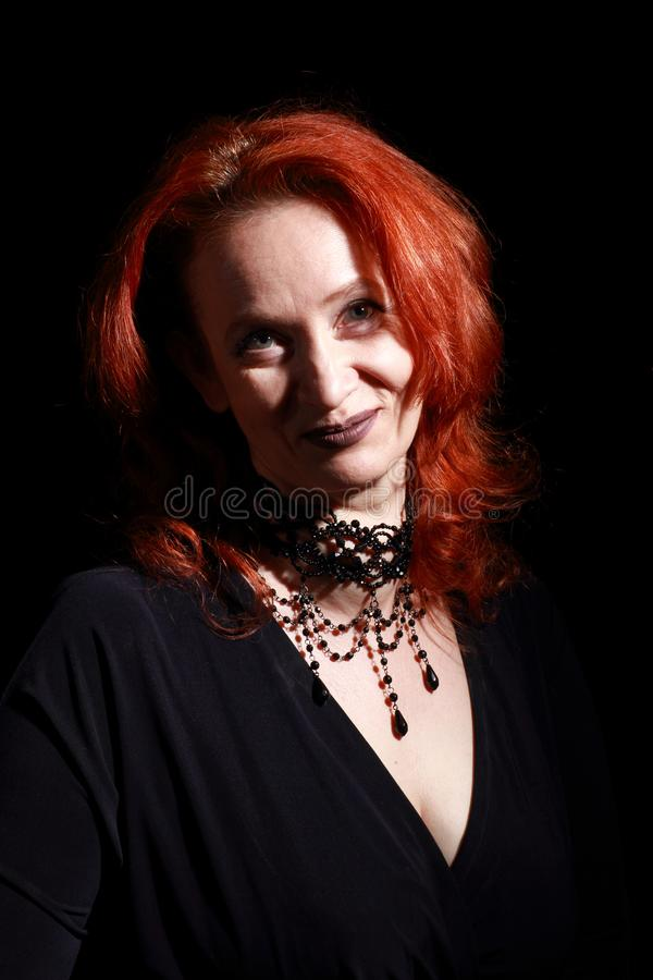 Vertical portrait of fine emotional redhead witch. Magical decorations and live expressions. Black wizard background royalty free stock images