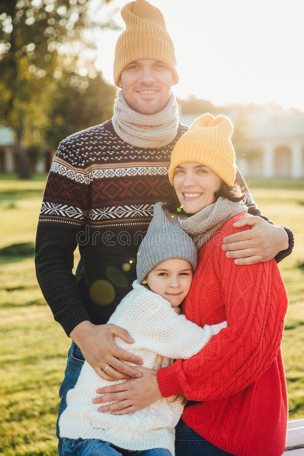 Vertical portrait of friendly family couple stand together, embrace each other, have good relationships, enjoy sunny weather. Hand royalty free stock image