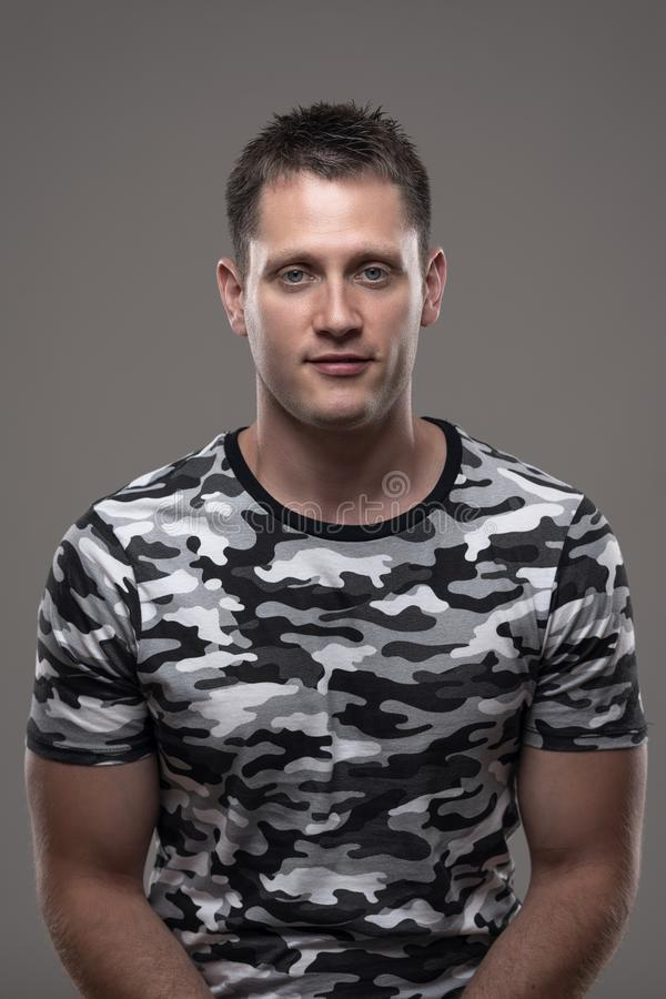 Vertical portrait of happy young relaxed adult man smiling at camera in camouflage army t-shirt. On gray background stock photography