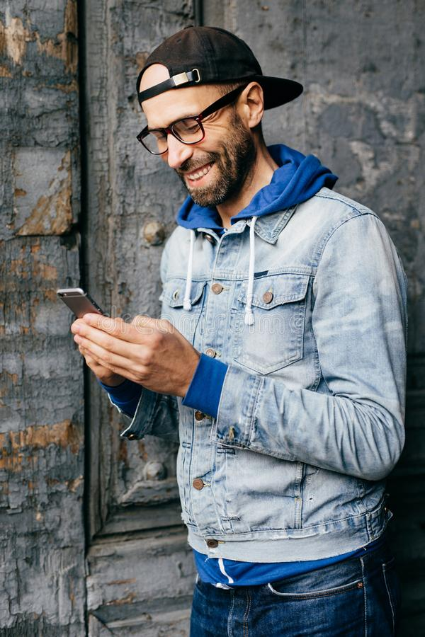 Vertical portrait of hipster guy in denim shirt, cap and eyewear holding modern telephone in his hands having glad expression whil royalty free stock image
