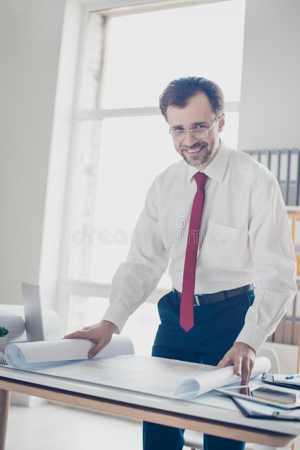 Vertical portrait of mature smart smiling architect analyzing bl stock image