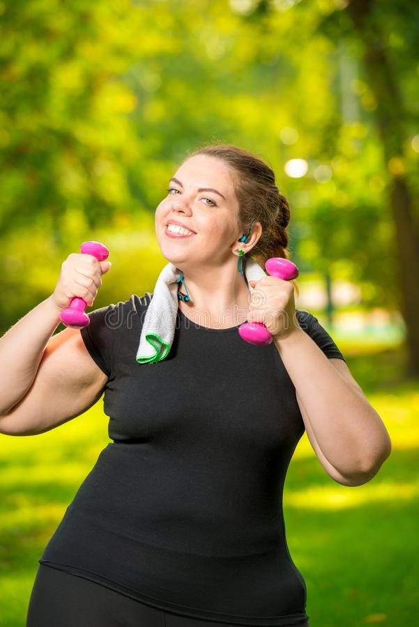 Vertical portrait oversize woman in headphones with dumbbells in hand is engaged in sports royalty free stock images