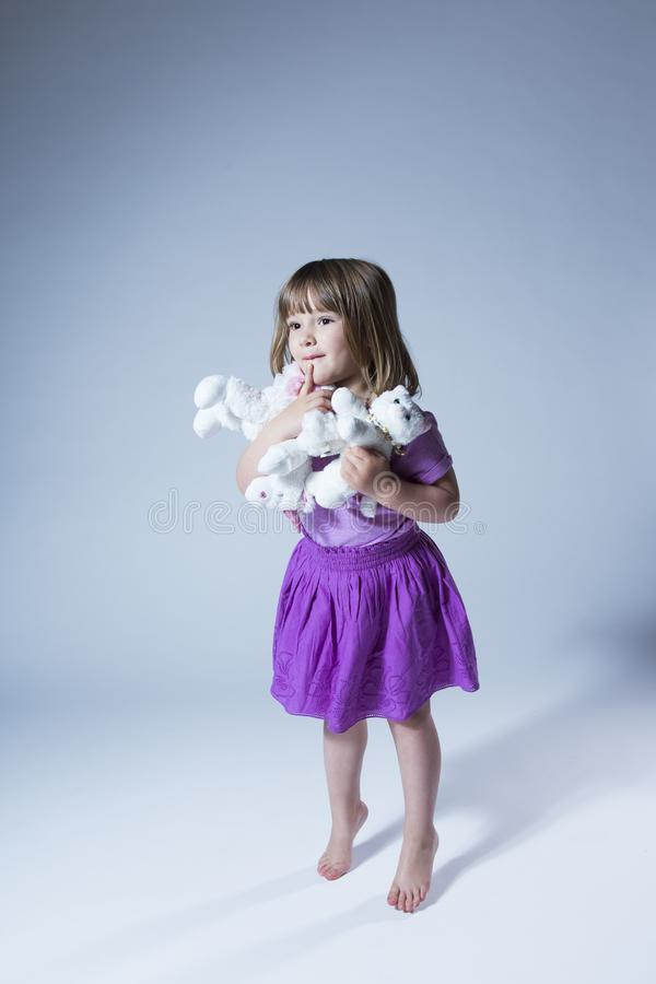Vertical portrait of pretty little barefoot girl dressed in purple skirt and top holding an armful of plush toys stock image