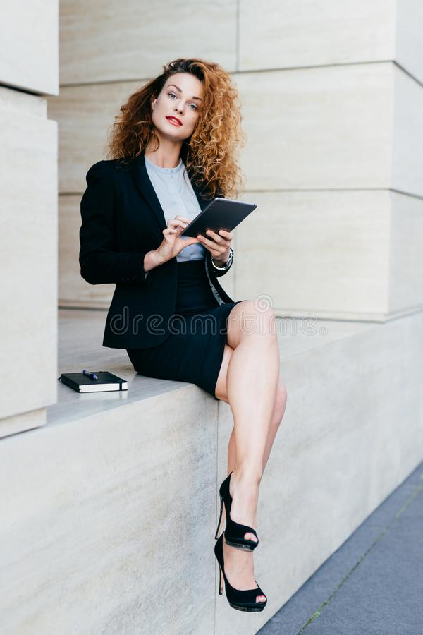 Vertical portrait of pretty slim woman with curly hair, wearing black jacket, skirt and high-heeled shoes, using modern tablet com royalty free stock photography