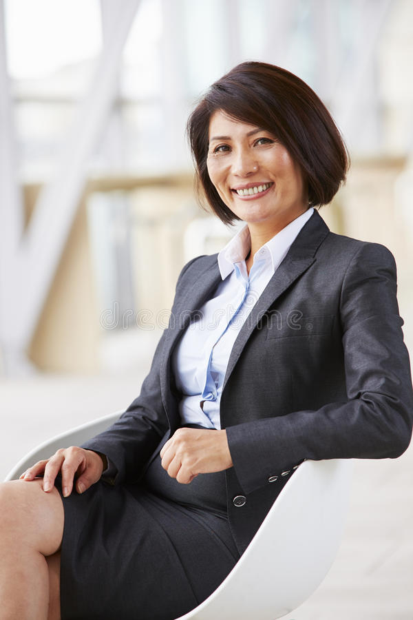 Vertical portrait of smiling Asian businesswoman, sitting royalty free stock image
