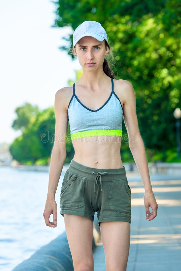 vertical portrait of a sports woman on the embankment in a city park royalty free stock photos