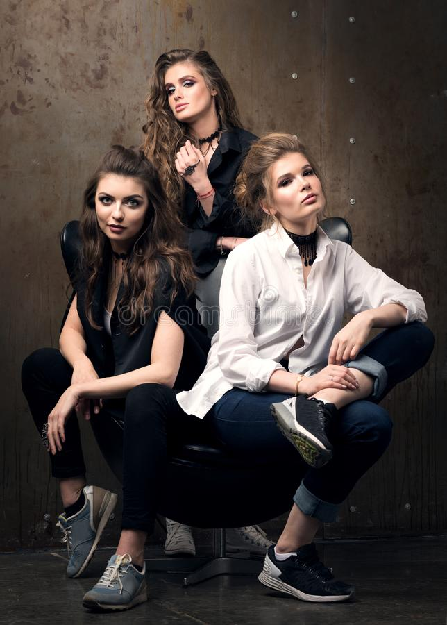 Vertical portrait of three beautiful young women posing on a chair royalty free stock image