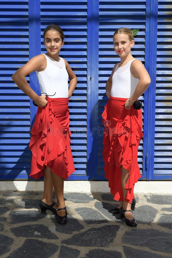 Vertical portrait of two girls in a flamenco position. They are in a symmetrical position with the typical handkerchief, looking. Vertical portrait of two girls royalty free stock photos