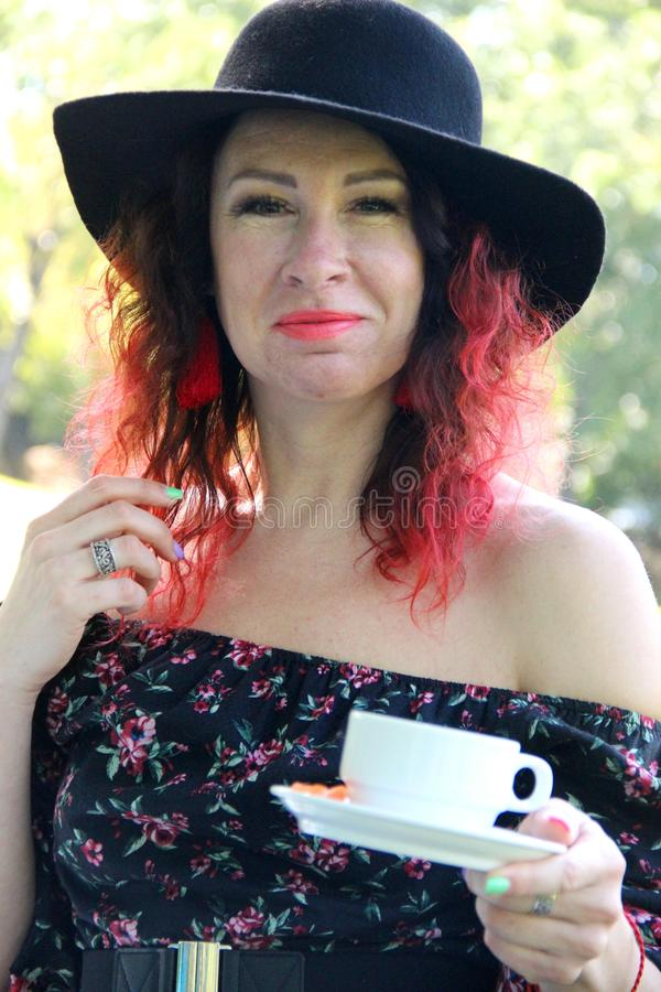 woman with red curls of hair, dressed in a black dress and a black hat, with a Cup of tea in her hand, vertical stock photography