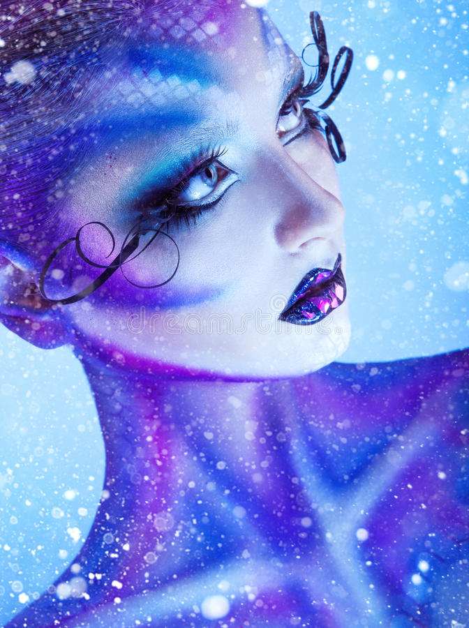 Vertical portrait of young adult girl with creative body art loo. King away with snow on background in studio royalty free stock photos