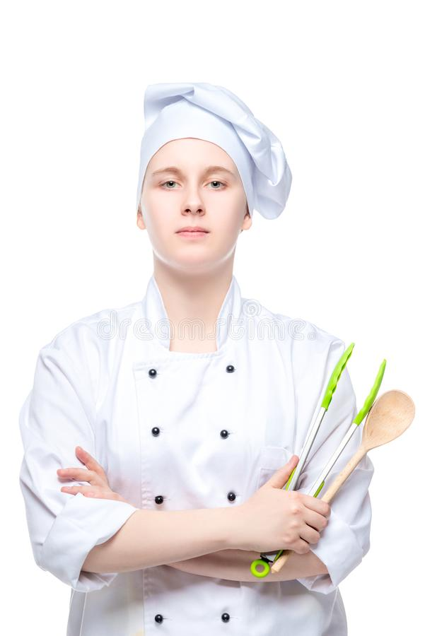 vertical portrait of a young cook with a spoon and culinary tongs isolated on white royalty free stock photography