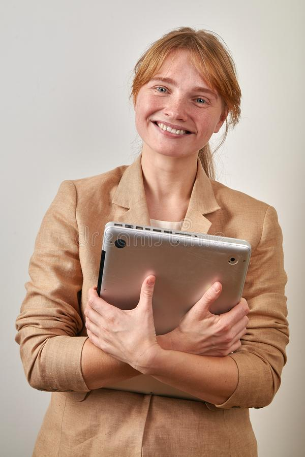 Portrait of young girl with ginger hair in ponytail dressed in casual beige jacket holding a laptop computer royalty free stock photo