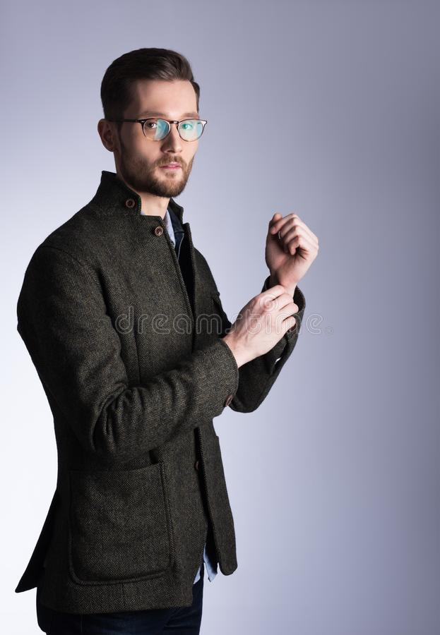 Vertical portrait of a young handsome man in coat. Glasses and b royalty free stock photos