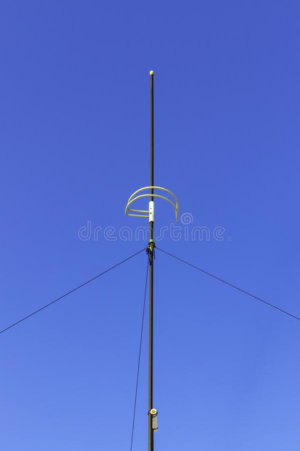Vertical radio antenna installed on the roof of the house against the blue sky royalty free stock photography