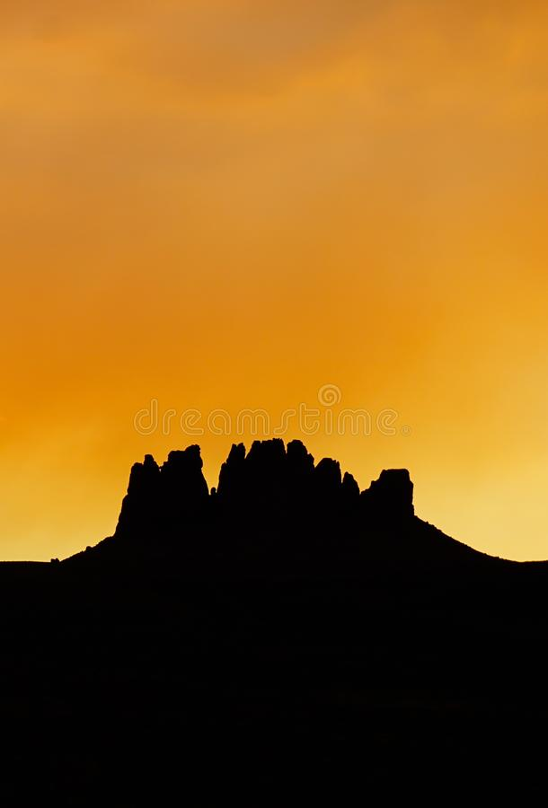 Vertical rock mesa silhouette under an orange sunset sky. In the northern Arizona desert royalty free stock images