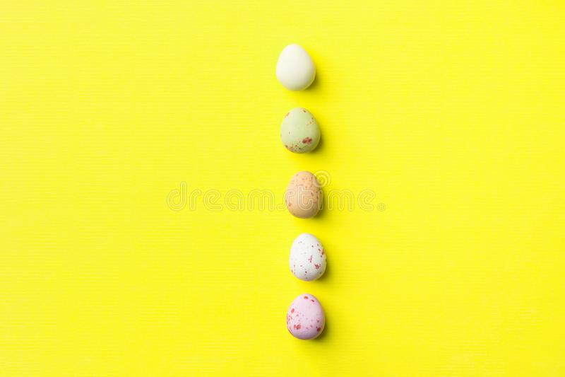 Vertical row of multicolored speckled chocolate eggs on light yellow background with linen paper texture. Easter greeting card royalty free stock images