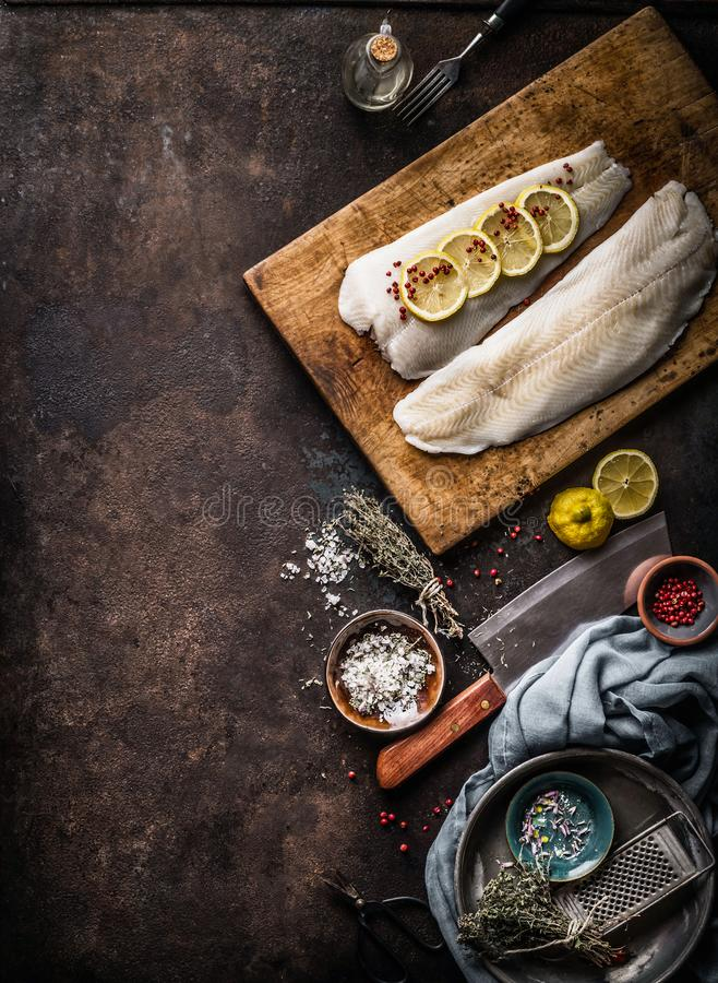 Vertical seafood background with raw cod fillet with lemon slices and herbs on rustic background with cutting board and knife, top. View. Fish cooking stock image