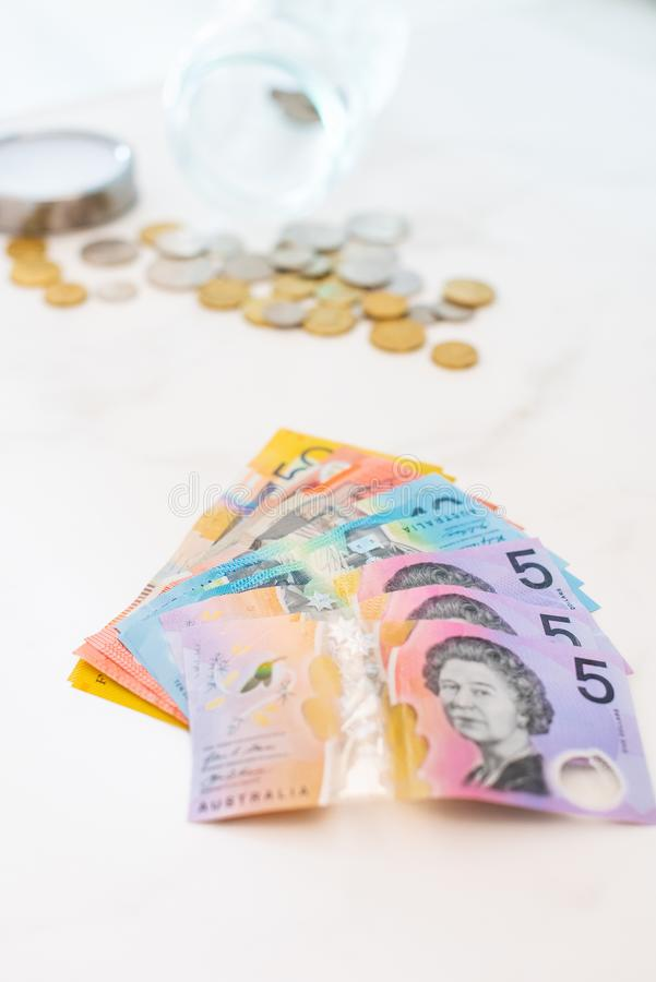Vertical selective closeup shot of Australian dollar banknotes and coins stock photography
