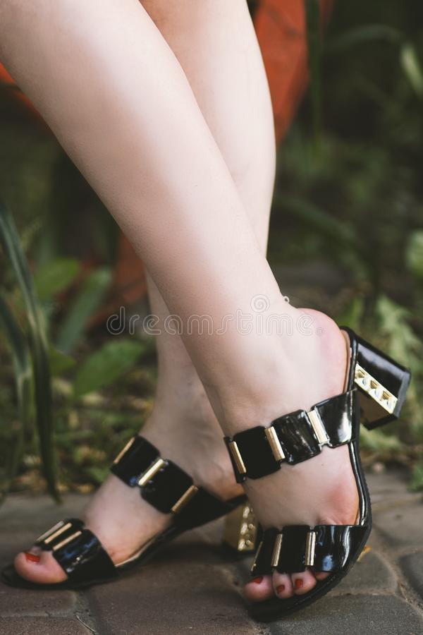 Vertical selective closeup shot of a Caucasian female wearing black and gold open-toe sandals. A vertical selective closeup shot of a Caucasian female wearing royalty free stock photos