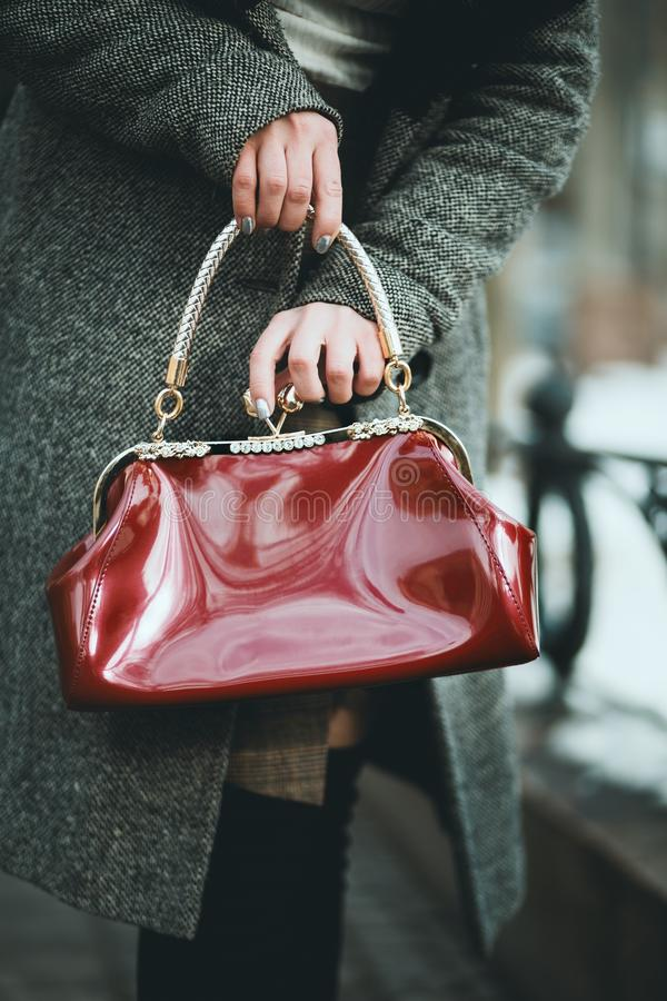 Vertical selective closeup shot of a female wearing gray long coat holding red handbag. A vertical selective closeup shot of a female wearing gray long coat stock images