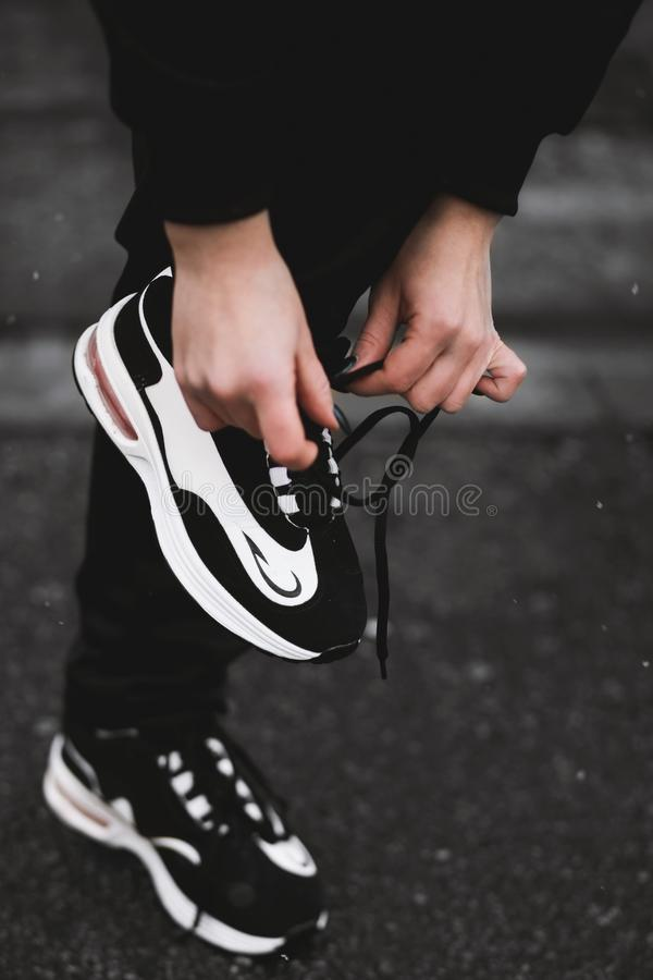 Vertical selective closeup shot of a person tying the laces of black and white sneakers. A vertical selective closeup shot of a person tying the laces of black royalty free stock photo