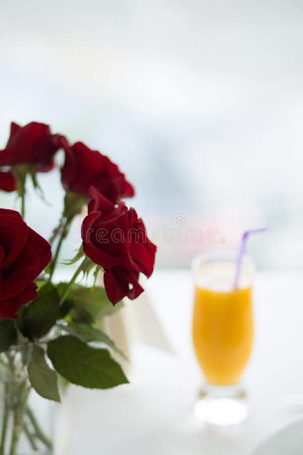 Vertical selective closeup shot red roses on the blurry background of orange juice in a glass. A vertical selective closeup shot red roses on the blurry royalty free stock photos