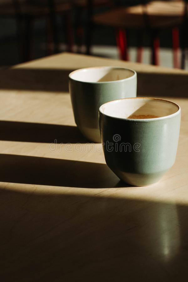 Vertical selective closeup shot of white ceramic coffee cups on a wooden surface. A vertical selective closeup shot of white ceramic coffee cups on a wooden royalty free stock image