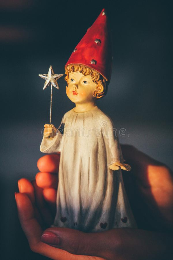 Vertical selective focus shot of a figurine with red hat and star wand royalty free stock photos