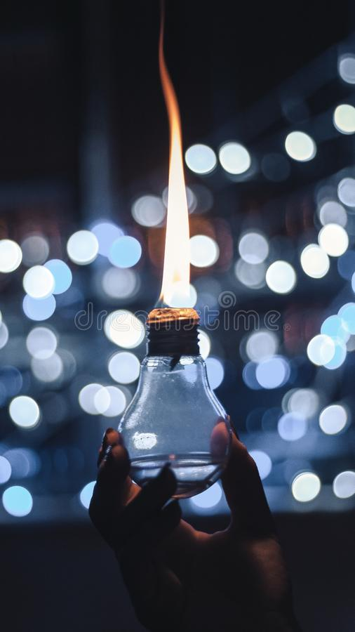 Vertical selective focus shot of a person holding a burning oil lamp stock image