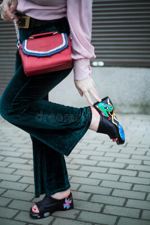 Vertical selective shot of a female wearing blue pants, sandals with random colors and a red bag. A vertical selective shot of a female wearing blue pants stock photo