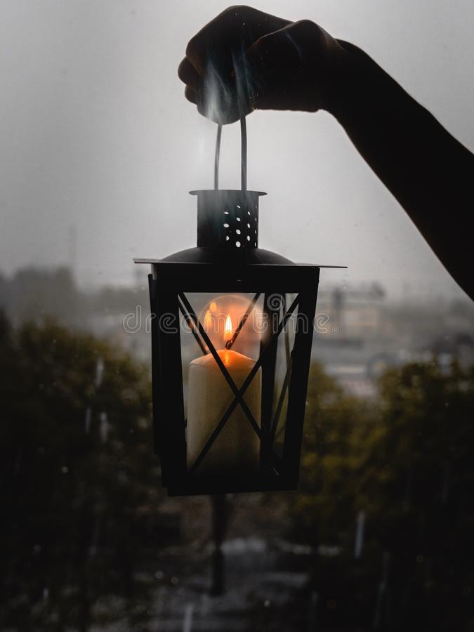Vertical selective shot of a person holding black candle lantern. A vertical selective shot of a person holding black candle lantern royalty free stock photo