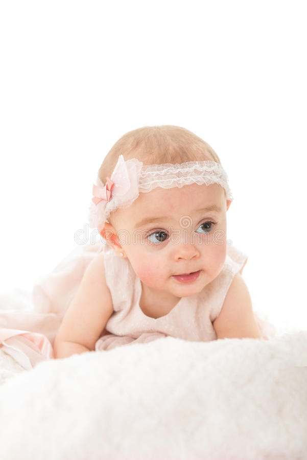 Vertical shot of adorable baby girl looking away. Shot against white background with copy paste royalty free stock image