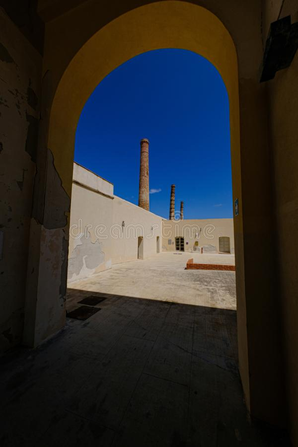 Vertical shot of an arched doorway with a view of towers in the distance on a sunny day royalty free stock photography