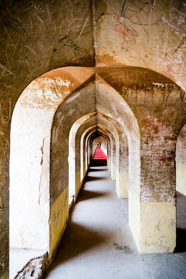 Vertical shot of an arched hallway of an ancient building. Vertical shot of an old and cracking arched hallway. Shot in the famed Labyrinth of the bara imambara stock photography