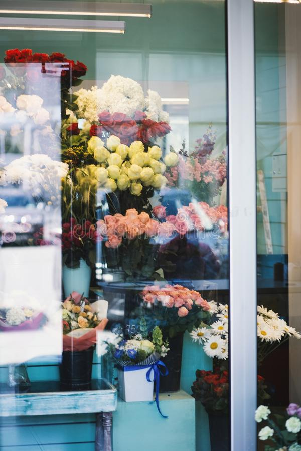 Vertical shot of assorted flowers of different colors in vases inside of a flower shop. A vertical shot of assorted flowers of different colors in vases inside stock photos