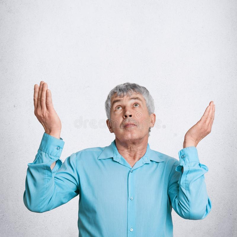 Vertical shot of attractive grey haired mature elderly male prays and asks God for something desirable, looks upwards with great h. Ope, poses against white stock image