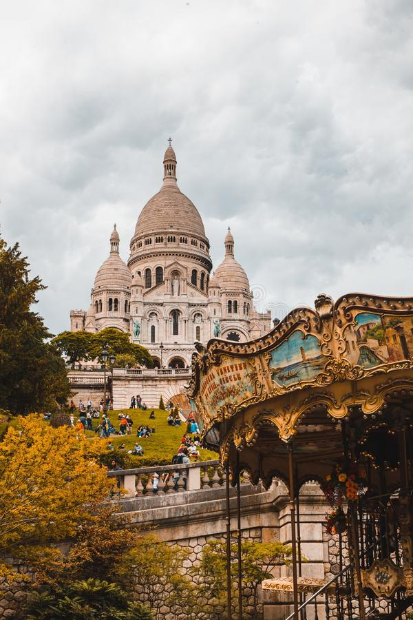 Vertical shot of The Basilica of the Sacred Heart of Paris or Sacre Coeur near a carousel in France royalty free stock images