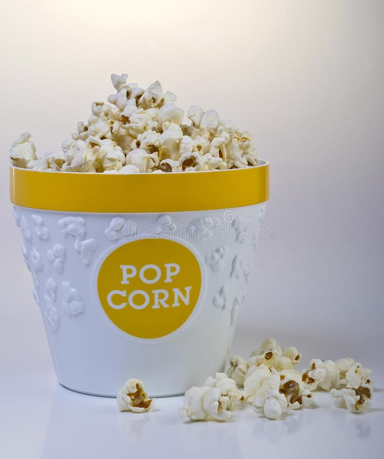 Vertical shot of a basket full of popcorn and some popcorn on around it on a white background stock image
