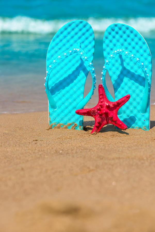 Vertical shot of beach shoes and starfish. On the sea royalty free stock photography
