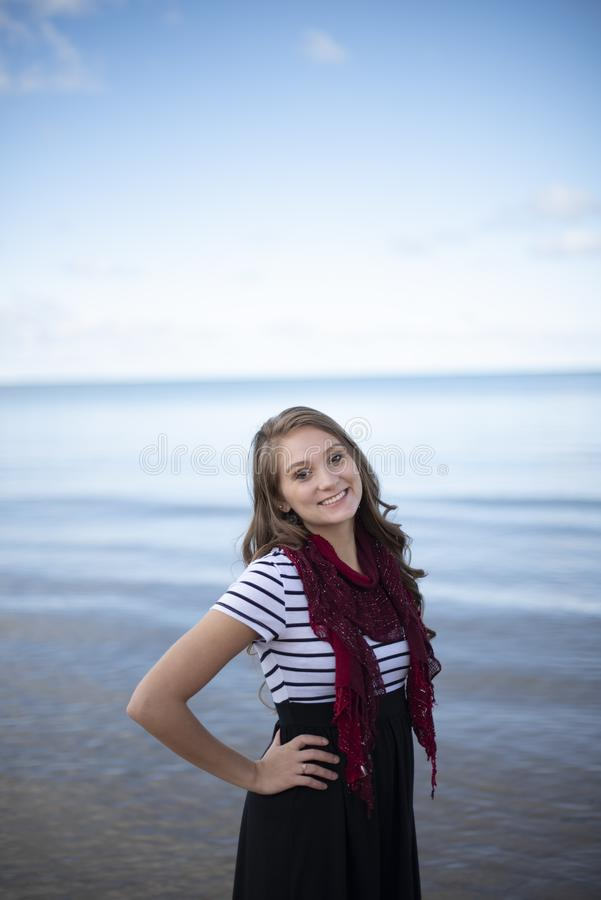 Vertical shot of a beautiful female with her hands on her waist while smiling at the camera stock images
