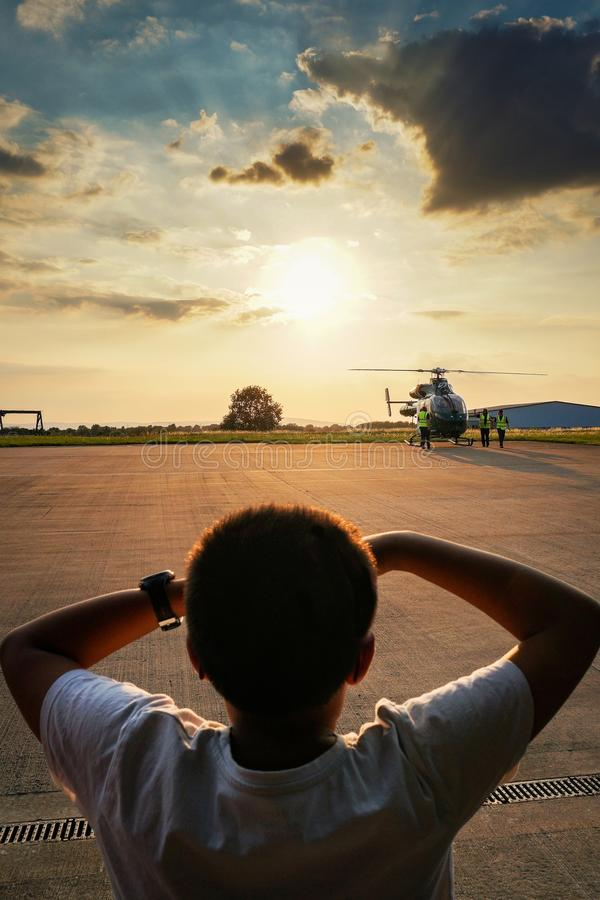 Vertical shot of beautiful large clouds in the sky and a young boy looking at the helicopter stock photos