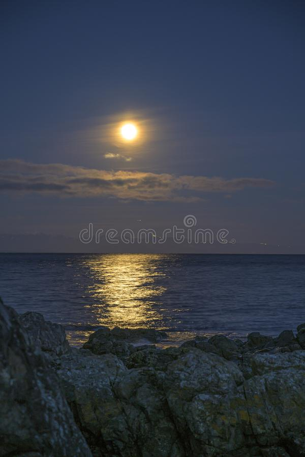 Vertical shot of a beautiful sea with the moon shining in the sky and reflecting on the water. A vertical shot of a beautiful sea with the moon shining in the royalty free stock photos