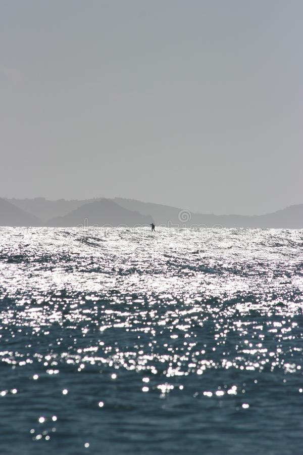Vertical shot of the beautiful sea with the sun reflecting on the water and a person on a boat. A vertical shot of the beautiful sea with the sun reflecting on royalty free stock photo