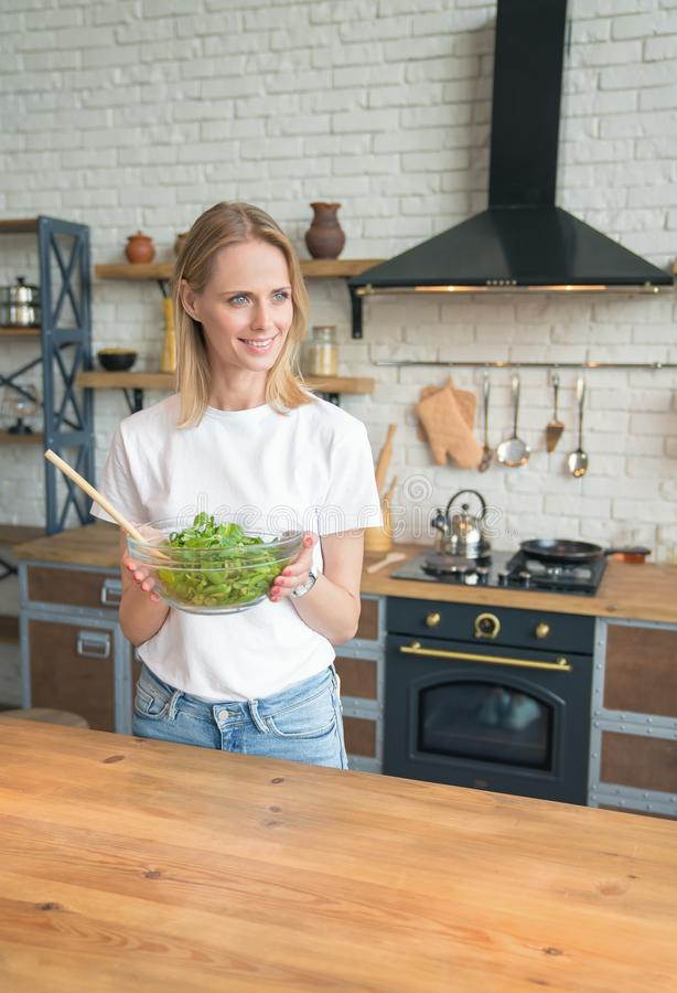 Vertical shot of beautiful of smiling woman holding salad in the kitchen. looking sideways. Healthy food. vegetable salad. Diet. royalty free stock photography