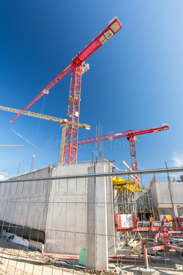 Vertical shot of big construction site with construction fence and cranes. Vertical shot of big construction site with construction fence, foundations and cranes royalty free stock photography