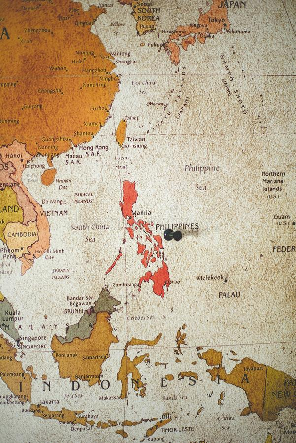 Vertical shot of a black pin on the Philippines country on the map stock photos